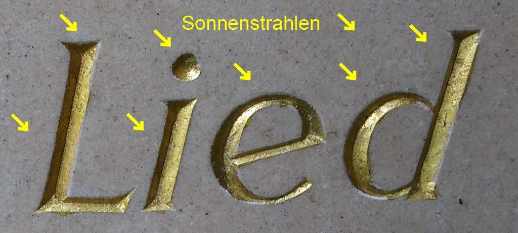 keilförmig eingemeißelte Schrift, mit markierter Richtung des Lichteinfalls